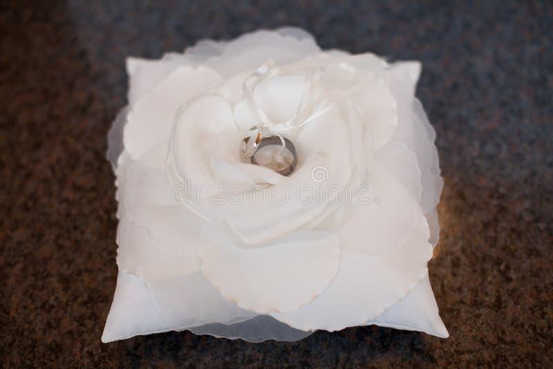 Trouwringen op een wit bloem en een hoofdkussen stock fotografie