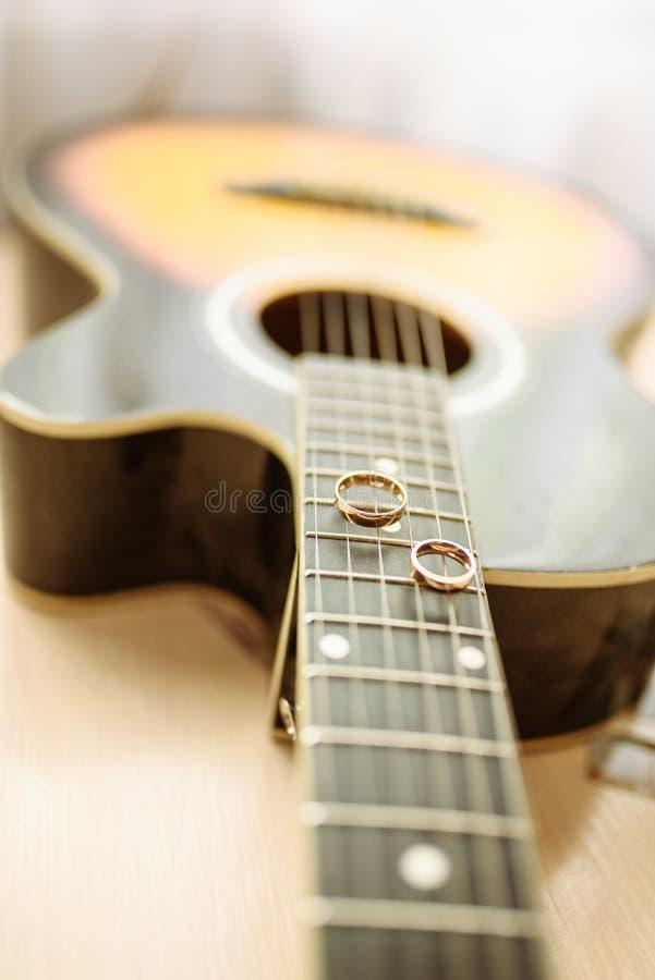 Trouwringen op gitaarkoorden royalty-vrije stock afbeeldingen