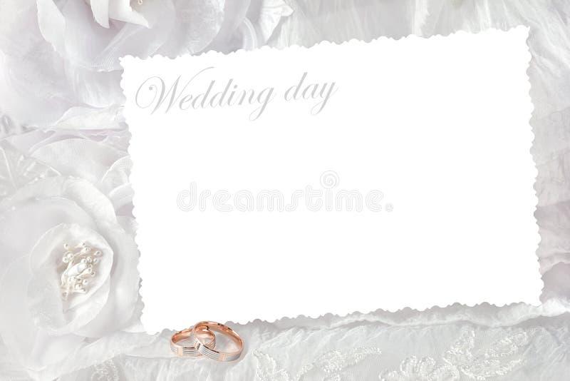 Trouwringen op huwelijkskaart, op een witte huwelijkskleding stock fotografie