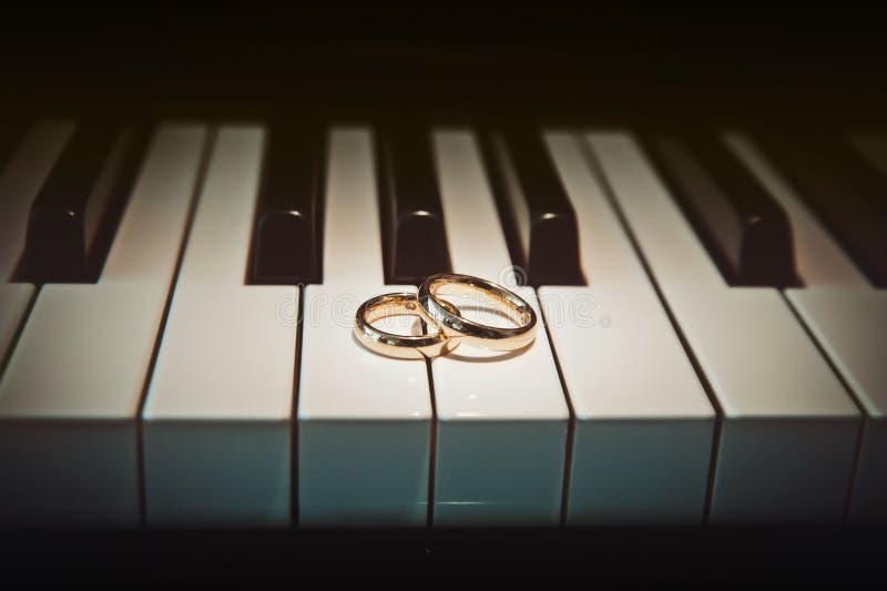 Trouwringen op piano stock afbeeldingen