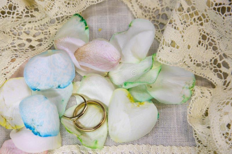 Trouwringen van mensen met regenboog namen bloemblaadjes toe royalty-vrije stock foto's