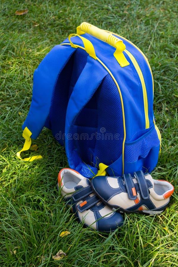 Trouxa azul da escola com sapatilhas, para preparar-se pelo ano escolar, uma trouxa na grama com sapatas imagem de stock royalty free