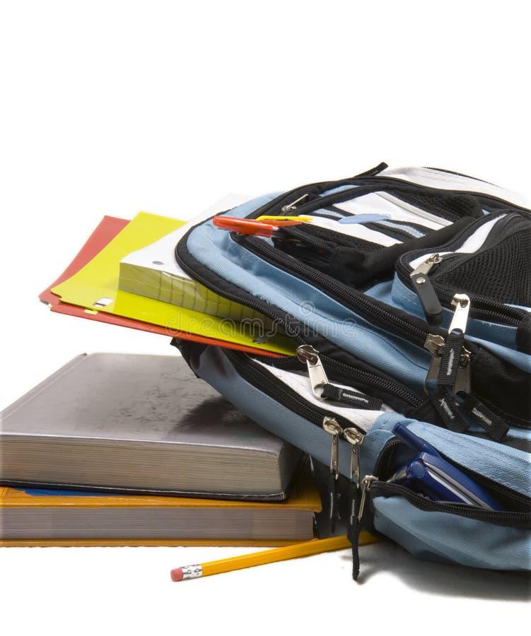 Trouxa azul da escola completamente de fontes de escola com livros de escola imagens de stock royalty free