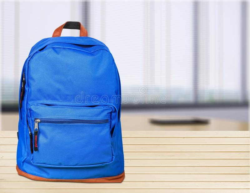 Trouxa azul da escola na tabela de madeira fotografia de stock royalty free