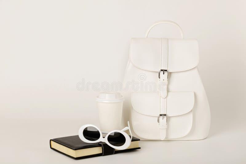 Trouxa, caderno e óculos de sol fêmeas brancos em um backgr branco foto de stock royalty free