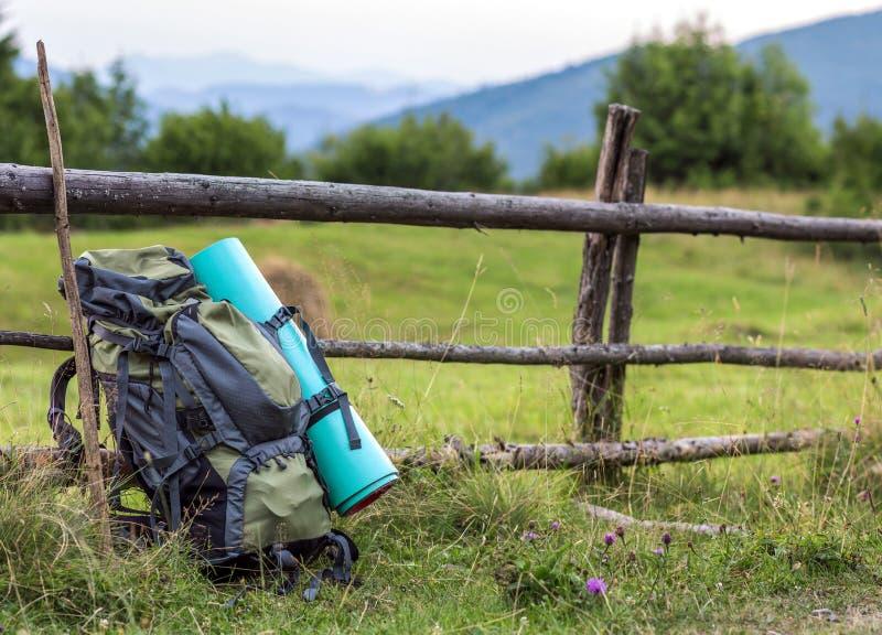 Trouxa de acampamento dos caminhantes que inclina-se na cerca de madeira velha Equ do turista imagem de stock