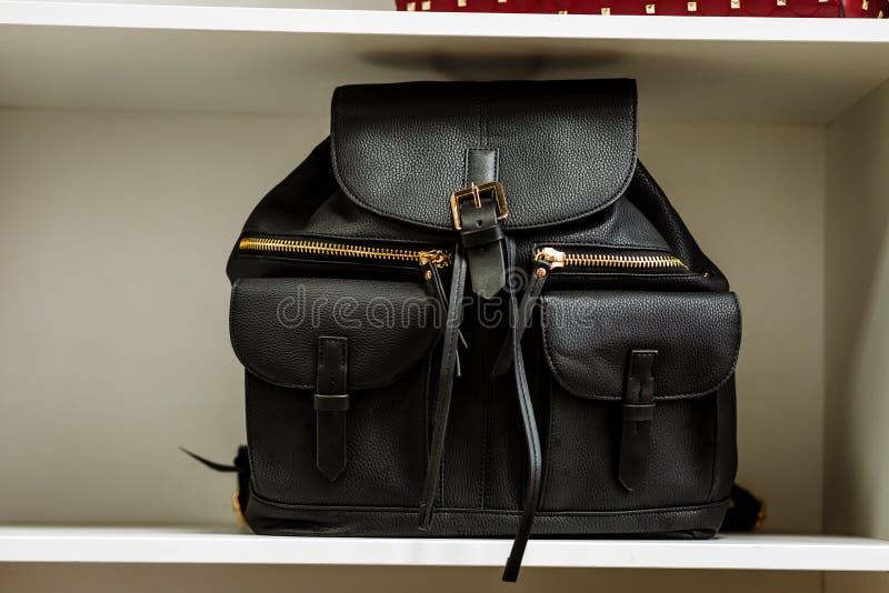 Trouxa de couro preta com os bolsos dourados do z?per em uma prateleira branca na loja imagem de stock