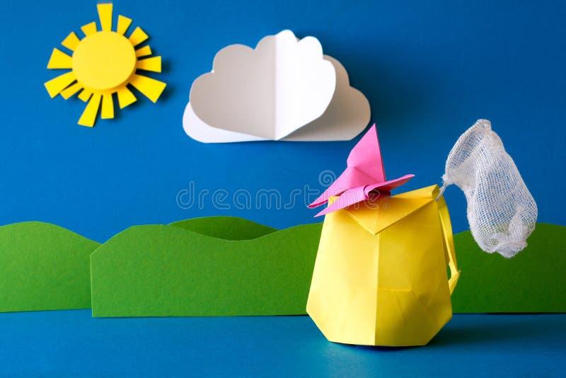 Trouxa de papel com rede da borboleta no campo de grama no fundo azul Aventura do verão Acampando e conceito da caminhada ou do t fotos de stock