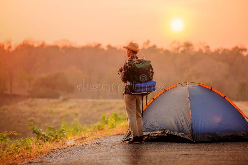 Trouxa do homem com a barraca no local de acampamento fotografia de stock royalty free