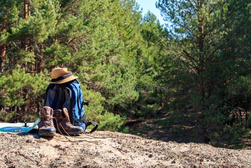 Trouxa do turista com caminhada de botas, de chapéu, de compasso e de mapa na clareira na floresta do pinho imagens de stock royalty free