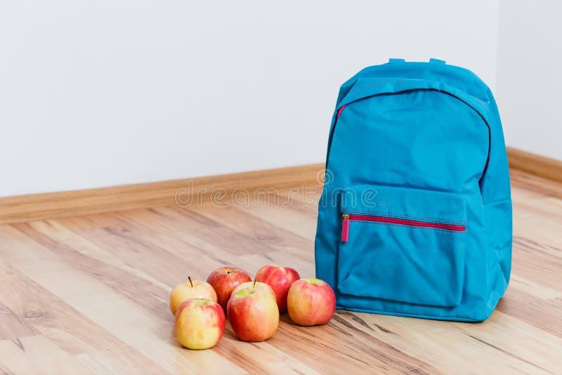Trouxa e maçãs azuis da escola fotos de stock royalty free