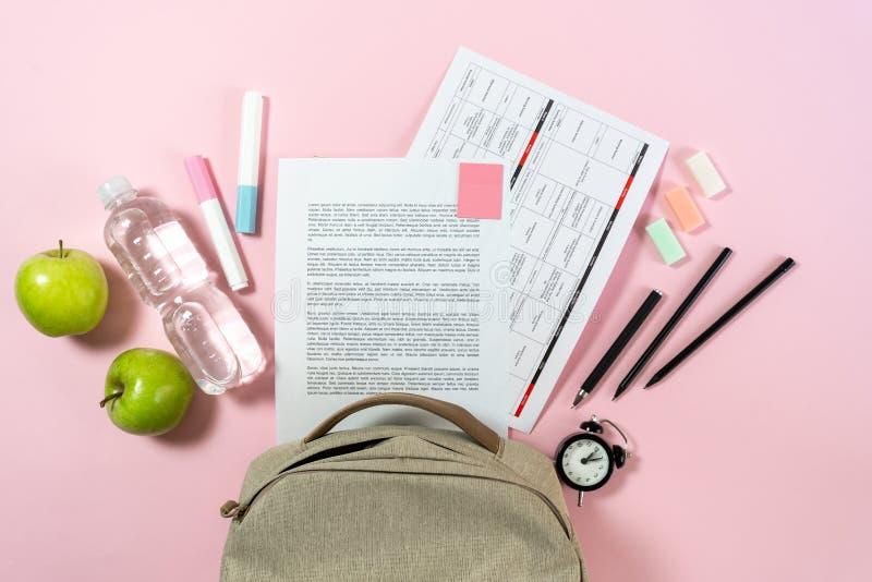 Trouxa, maçãs e artigos de papelaria da escola no fundo pastel cor-de-rosa fotos de stock royalty free
