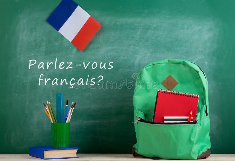 trouxa, quadro-negro com texto ' français parlez-vous? ' , bandeira das fontes de França, do livro e de escola foto de stock royalty free