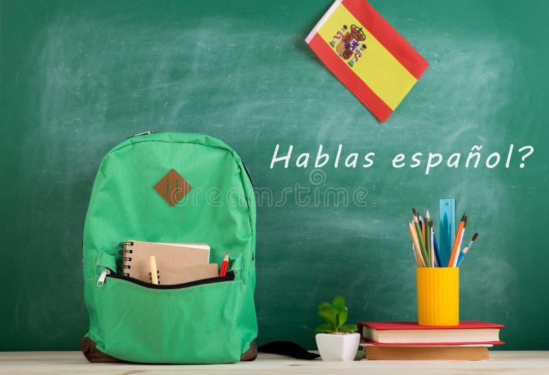 trouxa, quadro-negro com texto ' hablas español' , bandeira da Espanha, livros e fontes de escola imagens de stock