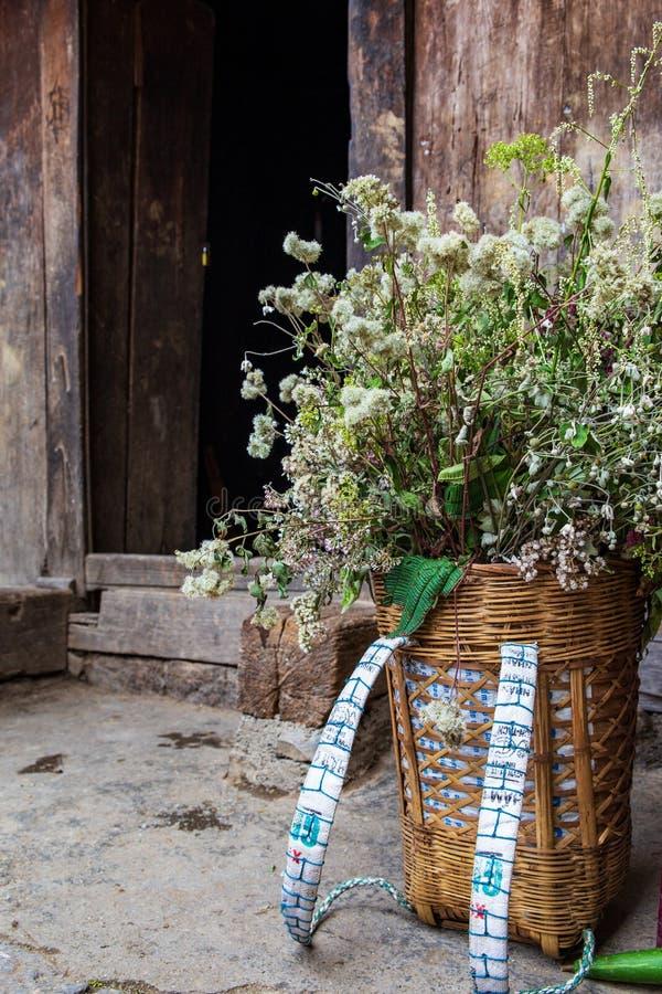 Trouxa tradicional da cesta de Hmong completamente das flores na entrada de uma casa tradicional do hmong na província de Ha Gian imagem de stock
