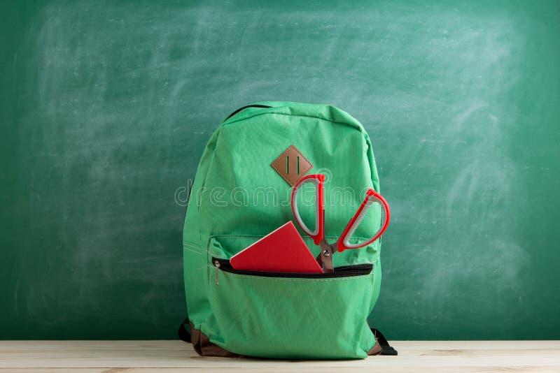 trouxa verde, tesouras vermelhas e caderno no fundo do quadro-negro imagens de stock