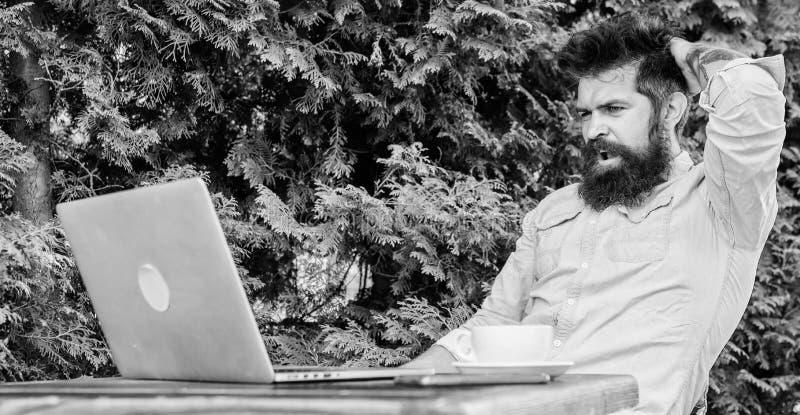 Trovi l'argomento per scrivere Internet praticante il surfing del computer portatile barbuto dei pantaloni a vita bassa Routine q fotografia stock
