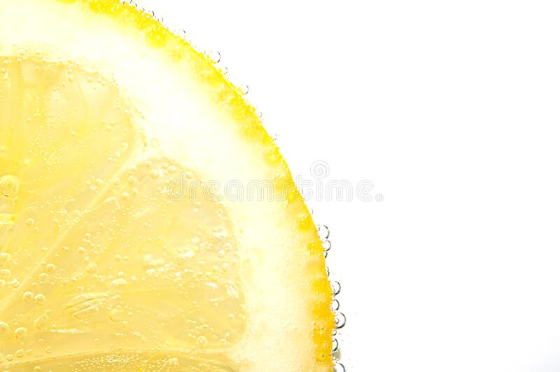 Trozo de limón fresco con burbujas de fizz imagenes de archivo