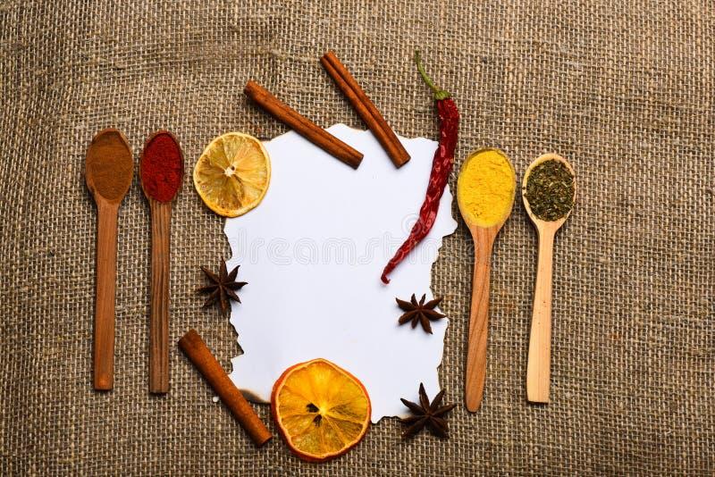 Trozo de papel en fondo de la harpillera Concepto culinario de la receta Canela, naranja secada y pimienta, anís de estrella alre foto de archivo libre de regalías