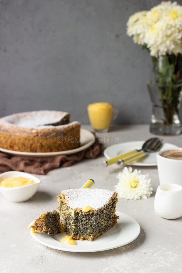 trozo de tarta de semillas de amapola con azúcar en polvo, crema y una taza de café fotografía de archivo