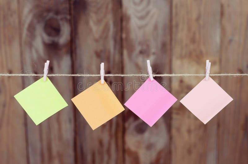 Trozos de papel coloreados que cuelgan en una cuerda fotos de archivo