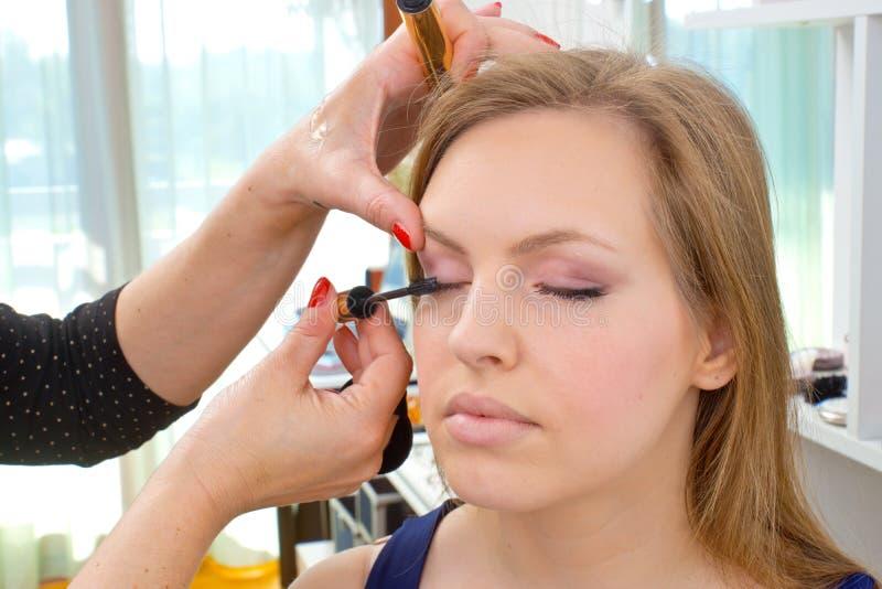 Truccatore che applica mascara sugli occhi della donna fotografie stock