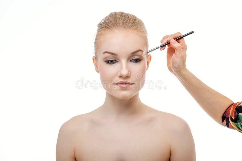 Truccatore che applica ombretto per la bella giovane donna su fondo bianco fotografia stock