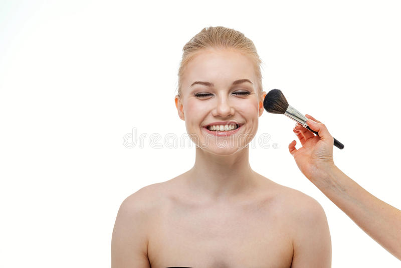 Truccatore che applica polvere per la bella giovane donna su fondo bianco immagini stock libere da diritti