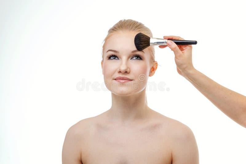 Truccatore che applica polvere per la bella giovane donna su fondo bianco immagini stock