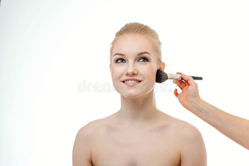 Truccatore che applica polvere per la bella giovane donna su fondo bianco fotografie stock libere da diritti