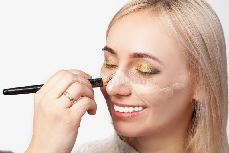 Truccatore che applica un fondamento color carne al fronte di una bionda con una spazzola durante le procedure cosmetiche immagine stock