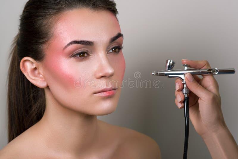 Truccatore che fa trucco professionale della giovane donna Dettaglio di trucco Ragazza di bellezza con pelle perfetta Bellezza, c immagine stock