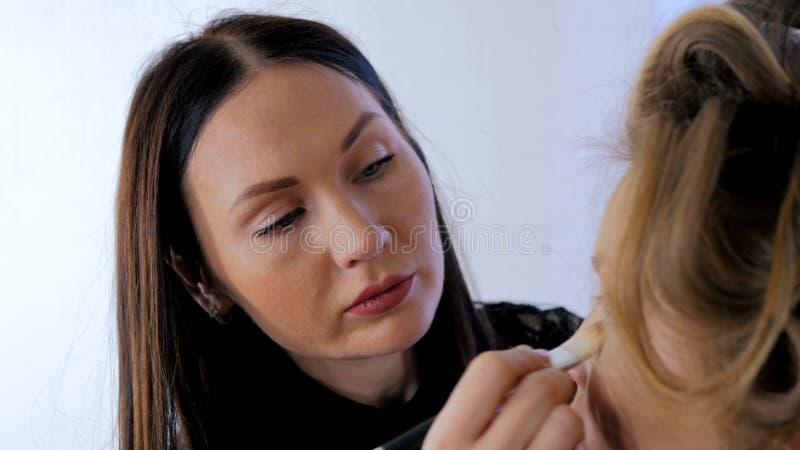 Truccatore professionista che applica trucco sul fronte del ` s della donna fotografia stock