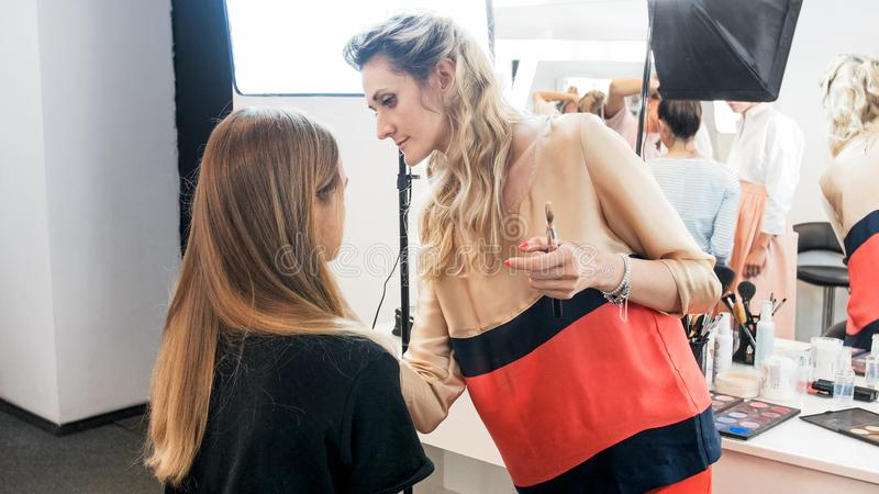 Truccatore professionista che lavora con il giovane modello in studio prima della sfilata di moda fotografia stock libera da diritti