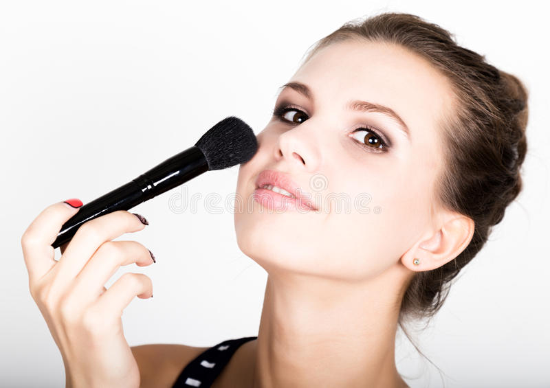 Trucco d'applicazione di modello femminile sul suo fronte Bella giovane donna che applica fondamento sul suo fronte con una spazz fotografie stock