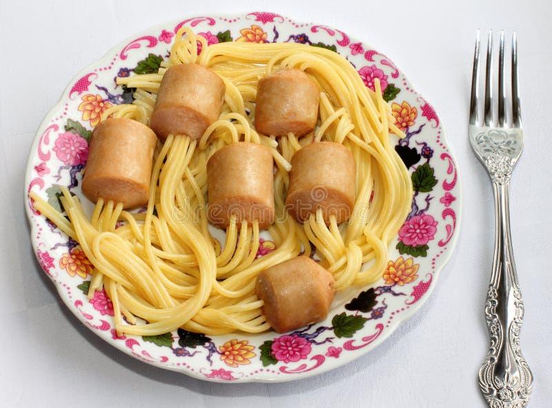 Trucco dal cuoco unico. Spaghetti attaccati in salsiccie. immagini stock libere da diritti