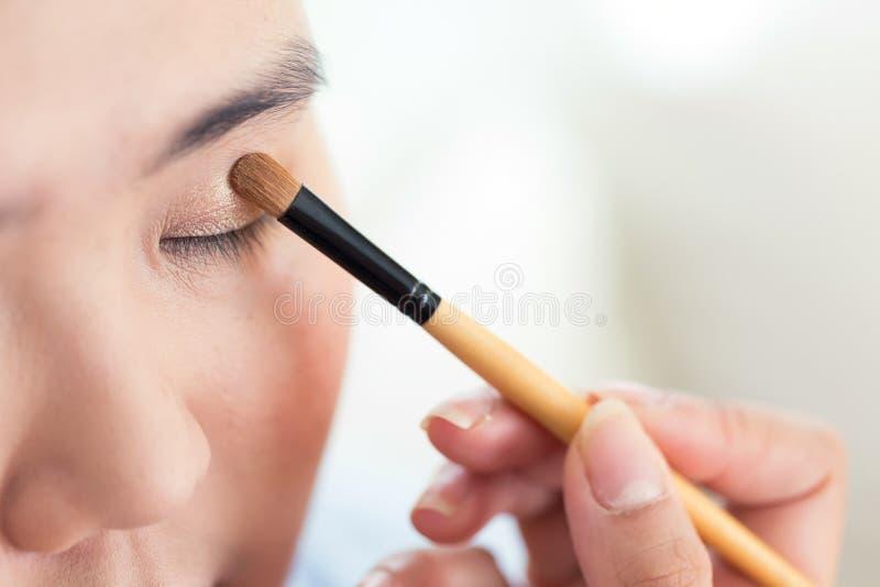 Trucco dell'occhio con la spazzola sulla donna graziosa fotografia stock libera da diritti