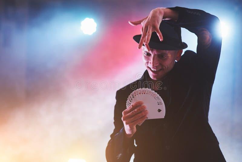 Trucco di rappresentazione del mago con le carte da gioco Magia o destrezza, circo, giocante Prestigiatore nella stanza scura con fotografia stock libera da diritti