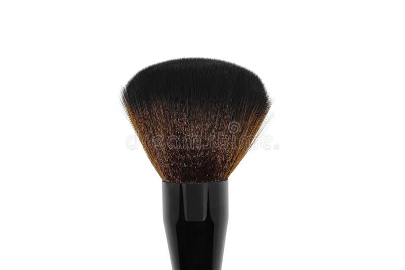 Trucco nero con la spazzola marrone dell'ombra sulla superficie bianca del fondo fotografia stock