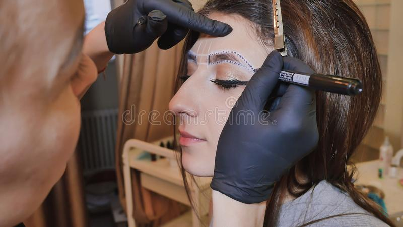 Trucco permanente Tatuaggio permanente delle sopracciglia L'applicazione del cosmetologo permanente compone sul tatuaggio del sop fotografie stock libere da diritti