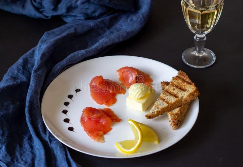 Trucha, mantequilla, pan y vino blanco Fondo oscuro fotografía de archivo libre de regalías