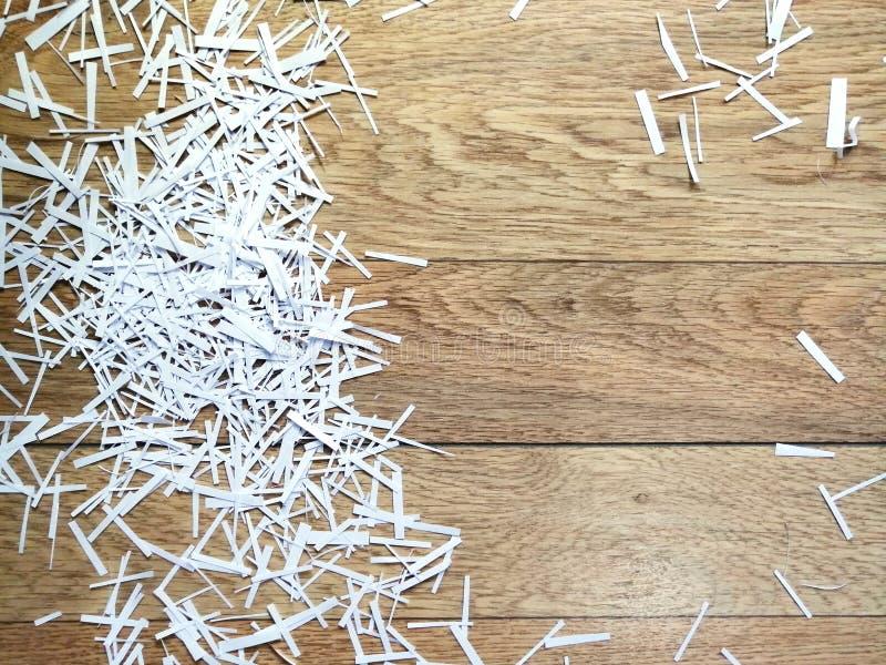 Trucioli di Libro Bianco su un fondo di legno immagini stock libere da diritti