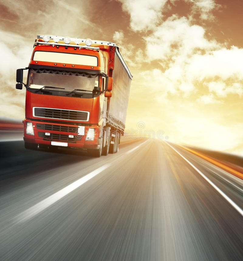 Truck. Red truck on blurry asphalt road under red sky with clouds and sunset light stock photos