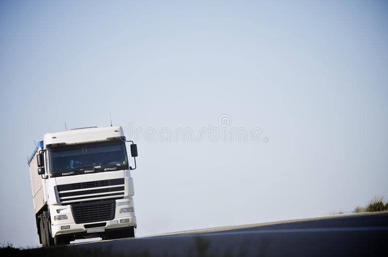 Truck. Circulating freight truck on a road with a clear blue sky royalty free stock image
