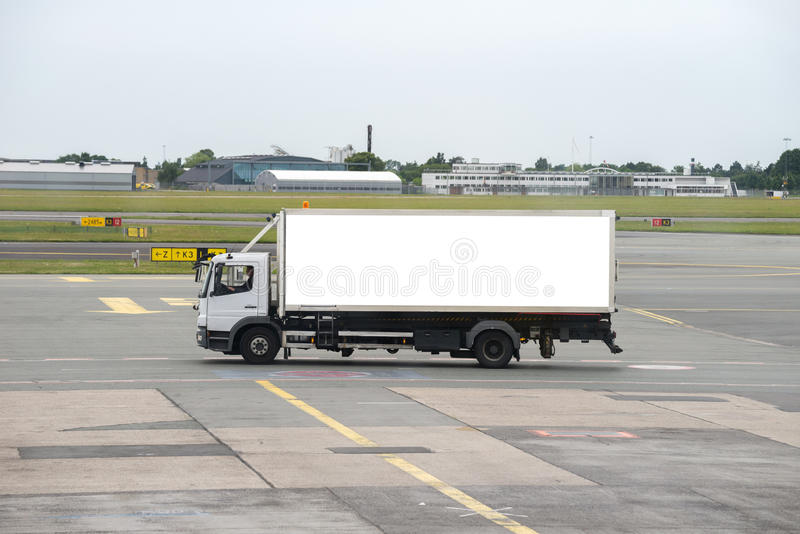 Truck on airport runway. White truck driving across airport runway stock image