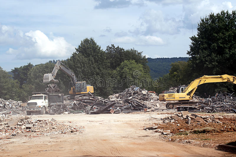Truck Being Loaded During Demolition Work. Dump truck being laded with rubble while demolition work is being done stock photo