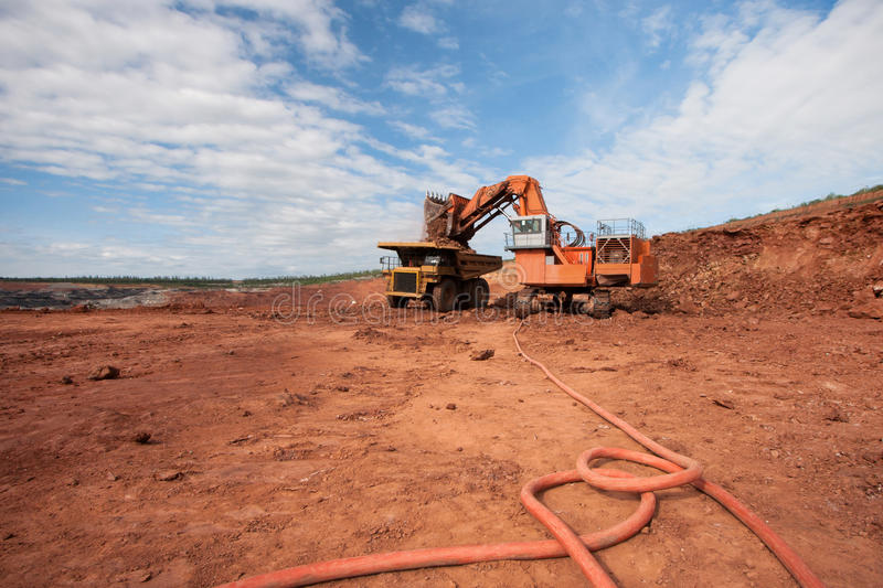 Truck is being loaded with ore at a mine site. Big Truck is being loaded with ore at a mine site royalty free stock photos