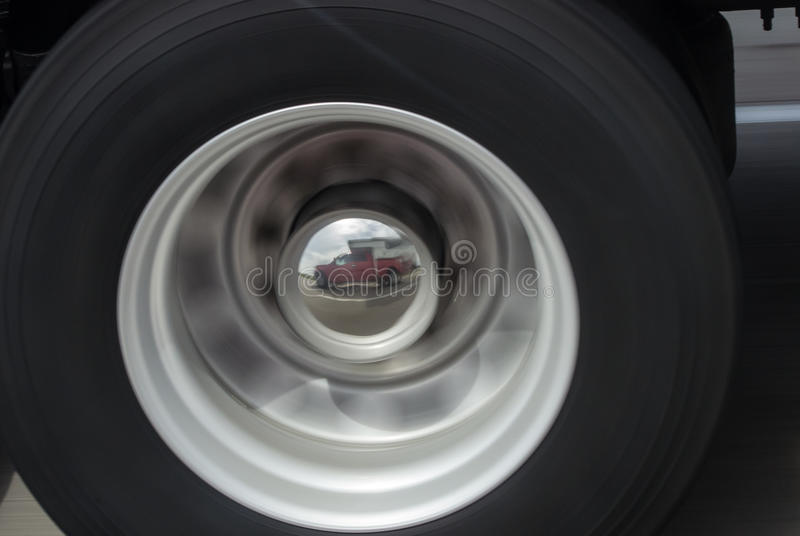 Truck and camper reflected in a hubcap. A red traveling truck with camper is reflected in the hubcap of a moving vehicle royalty free stock images
