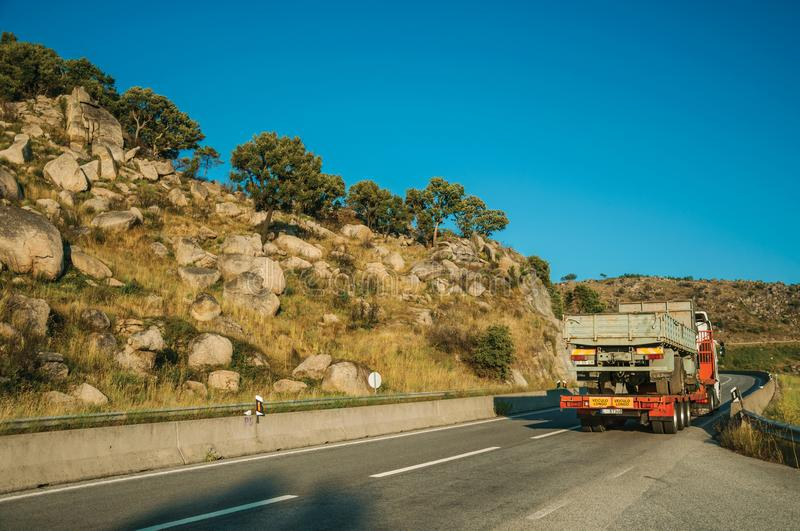 Truck carrying another truck by road on hilly landscape royalty free stock image