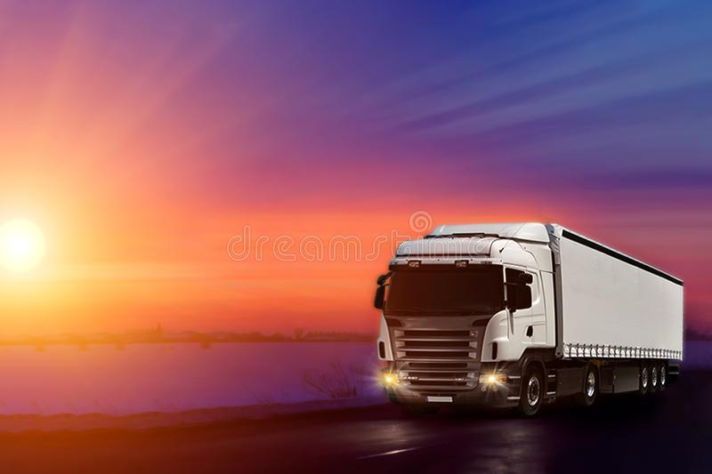 Truck with container on highway, cargo transportation concept. Sunset background with copy space royalty free stock photo